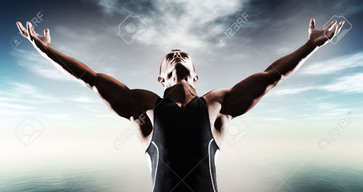 23389215-muscled-fitness-triathlon-athlete-arms-spread-wide-victory-standing-near-lake-stock-photo